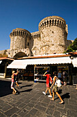People strolling over Platia Ippokratou with shops, Thalassini Gate in background, Rhodes Town, Rhodes, Greece, (Since 1988 part of the UNESCO World Heritage Site)