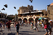 People strolling over busy Platia Ippokratou with shops and restaurants, flying doves, Thalassini Gate in background, Rhodes Town, Rhodes, Greece, (Since 1988 part of the UNESCO World Heritage Site)