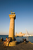 Women resting on base of column with deer Elafos at port entrance of Mandraki harbour (translated literally: fold), column with doe Elafia and fortress tower Agios Nikolaos in background, Rhodes Town, Rhodes, Greece