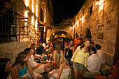 People sitting in outdoor areas of several bars of old town, Rhodes Town, Rhodes, Greece, (Since 1988 part of the UNESCO World Heritage Site)