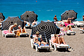 People sunbathing on sunloungers at main beach, Rhodes Town, Rhodes, Greece