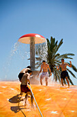 Four young men on a wet bubble, Faliraki Water Park, the biggest in Europe, Faliraki, Rhodes, Greece