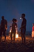 Young people standing on beach near a campfire, sunday party at Sundance Beach Bar, Gennadi beach, Gennadi, Rhodes, Greece