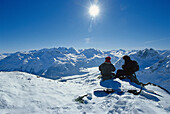 Two people sitting in the snow, Corviglia, St. Moritz, Engadin, Grisons, Switzerland, Europe