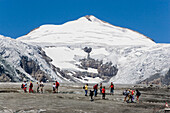 People walking on Pasterze glacier (the biggest glacier of Austria), Großglockner (3798 m, highest mountain of Austria) in background, Franz Josephs Höhe (2369 m), Carinthia, Austria