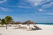 Menschen entspannen am Strand des Bucuti Beach Resort am Eagle Beach, Aruba, ABC-Inseln, Niederländische Antillen, Karibik