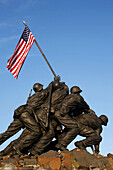 War memorial with flag in front of blue sky, Iwo Jima Memorial, Arlington, Virginia, USA