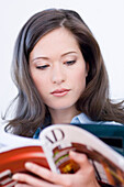 Young woman reading a journal