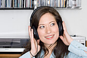 Young woman listening to music about earphones