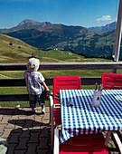 Boy standing on terrace of Alpine hut, Simmental vallley, Bernese Alps, Canton of Bern, Switzerland