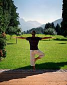 Man exercising yoga in a garden, Leogang, Salzburg (state), Austria