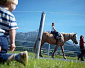 Girl sitting on horse, mother holding lead, Leogang, Salzburg, Austria