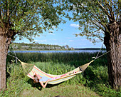 Frau liegt in einer Hängematte am Seeufer, Hotel Neuklostersee, Nakenstorf, Mecklenburg-Vorpommern, Deutschland