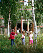 Children in the garden waving to mother at the window of a Wellness Hotel, guests in the garden of Spa Hotel Seehotel Neuklostersee, Mecklenburg - Western Pomerania, Germany