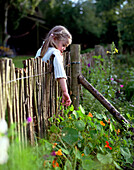Girl looking over the fence in the kitchen garden, spa area of Seehotel Neuklostersee, Mecklenburg - Western Pomerania, Germany