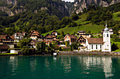 View over Lake Urnersee, part of Lake Lucerne to Bauen, the smallest village in Uri, with the parish church of St. Idda, Bauen, Canton of Uri, Switzerland