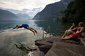 Boy jumping into water of Lake Urnersee, part of Lake Lucerne, Bauen, Canton of Uri, Switzerland