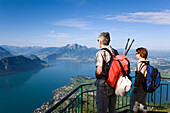 Mature adult couple at Kanzli vantage point on Rigi (1797 m, Queen of the Mountains) and looking over Lake Lucerne with Weggis, mount Bürgenstock and mount Pilatus (2132 M) in the background, Rigi Kaltbad, Canton of Schwyz, Switzerland