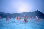 Iceland, Blue Lagoon near Rejkjavik, boys with white facial mask in thermal pool, fog