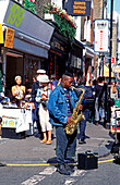 UK , London, Portobello Road, street musician with saxophone