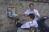 Hairdresser with client, open air, Hanoi, Vietnam