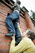 Boy giving friend a bunk-up over a wall