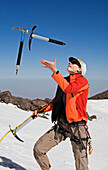 Mid adult woman juggling with ice axes, High Atlas Mountains, Morocco