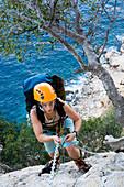 Young woman climbing, holding, chain, Il Sentiereo Selvaggio Blu, Golfo di Orosei, Sardinia, Italy, MR