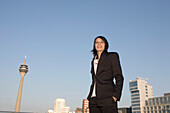 Young business woman in front of city skyline, Media Harbour with television tower and Neuer Zollhof, architecture of Frank O.Gehry, Düsseldorf, state capital of North-Rhine-Westphalia, Germany