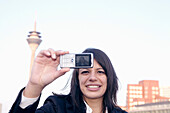 Young business woman making a selfportrait with mobile phone, in front of the city skyline, Media Harbour, Düsseldorf, harbor, television tower, Zollhof, architecture of Frank O.Gehry, state capital of NRW, North-Rhine-Westphalia, Germany