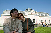 Mature adult couple sitting in front of the Benrath castle, Düsseldorf, state capital of NRW, North-Rhine-Westphalia, Germany