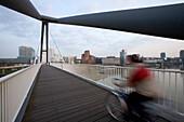 Cyclist on the footbridge at the Media Harbour in Düsseldorf, state capital of NRW, North-Rhine-Westphalia, Germany