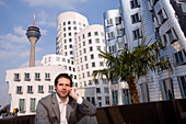 Young business talking on his mobile phone in front of the Neuer Zollhof, modern architecture from Frank Gehry, with television tower in the background, Media Harbour, Düsseldorf, state capital of NRW, North-Rhine-Westphalia, Germany