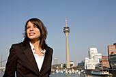 Young business woman in front of city skyline with television tower, Neuer Zollhof in the background, Media Harbour, architecture from Frank O.Gehry, Düsseldorf, state capital of NRW, North-Rhine-Westphalia, Germany