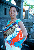 portrait of an indonesian woman, Lovina beach, Bali, Indonesia, Asia, smiling in camera, keeping sarongs in her hands, tourism, tourists, selling, source of income, colourful, friendly, simple lifestyle, tradition, culture, traditional cloth