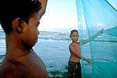 Young fishermen from Gili Trawangan practising with fishing net, Lombok, Indonesia