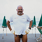 bath attendant in Levanto, Ligurien, Italy, wearing gloves, security, working, to position deckchais, to put away deckchairs, putting his hands in his hips, smiling in Camera, friendly, looking for, closing time, end of work, after work, finish, glasses,