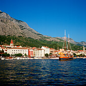 makarska, dalmatia, croatia, adriatic sea, vacation, travel, tourism, tourists, town right on the waterfront, water, boats, sightseeing, range of mountain in the back, view from the waterside, golden light