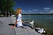Woman sitting at the lakeshore of Lake Starnberg, Bavaria, Germany