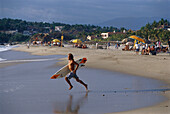 A surfer running into the water, Playa Zicatela, Puerto Escondido, Oaxaca, Mexico, America