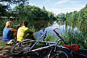 Two people, mountainbiking, having a rest at a lake, Fünfseenland, Five Lakes, bavaria, Germany