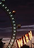 Big wheel and illuminated sign at night, Wiener Prater, Vienna, Austria