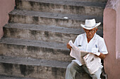 Mexican man sitting on the steps and reading a newspaper, Market, Merida, Yucatan Peninsula, Mexico