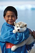 Inuit boy with sled dog, husky, Northwest Territories, Canada