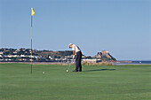 Mature adult, man, playing golf at a golf course at Gorey Golf Club, Orgeuil Castle, Jersey, Channel Islands, Great Britain