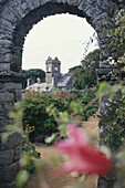 The Seigneurie Garden with view through an arch towards a church, Sark, Channel Islands, Great Britain