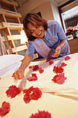Hotel personnel, woman putting flower petals on a bed, Hotel Oberoi, Holiday, Mauritius, Africa