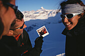 Man showing photograph to two friends, Snowshoeing, Mountain sports, Winter, Nebelhorn, Allgaeu, Bavaria, Germany
