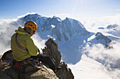 Mountaineer sitting on top of mount Dent du Geant (4012 m), Mont Blanc, France, Italy