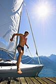 Man jumps out of a sailing boat onto the jetty, sailing on lake Traunsee, Upper Austria, Austria